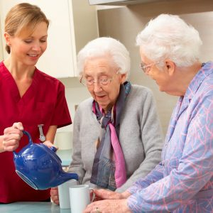 Nurse pours tea for two elderly women