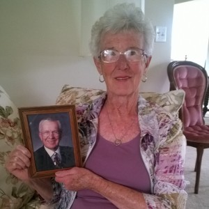 Senior woman holding photo of husband