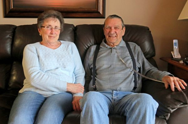 Karen and Bill Kelly sit side by side on their living room couch.