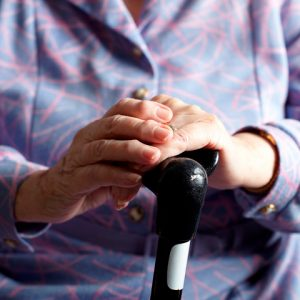 Hands holding onto a walking cane