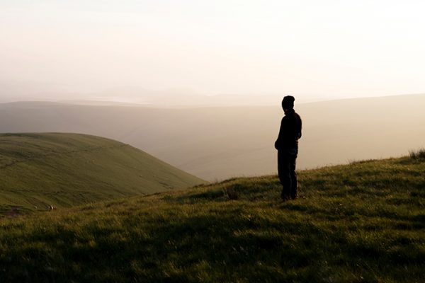 Silhouette of person on a hill