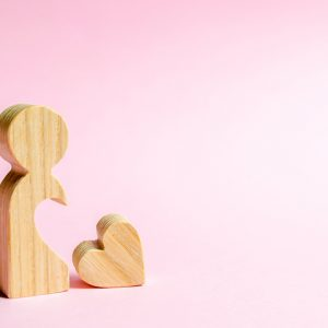Wooden person figure with heart shape cut out