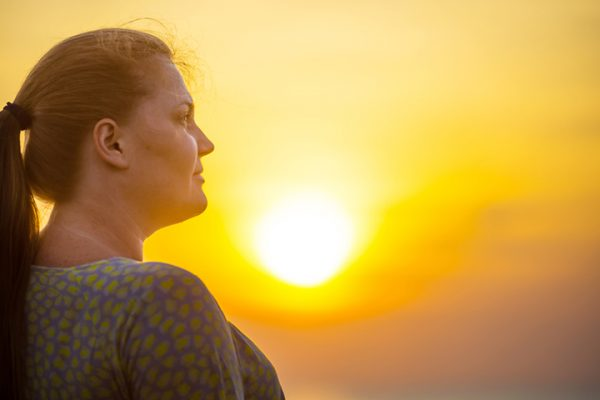 profile of woman with sunset in the background