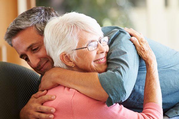 Middle aged man hugging elderly woman