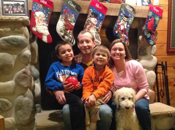 Neimeier family sitting in front of fireplace_christmas stockings above head