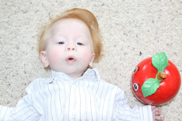 Gauge Neimeier_baby laying on his back next to an vintage apple toy
