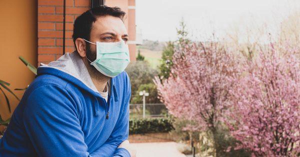 man standing on balcony outside wearing mask