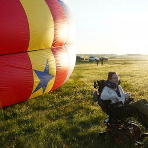 Mary Sluke sitting near a hot air balloon