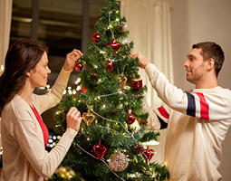 woman and man decorating a Christmas tree