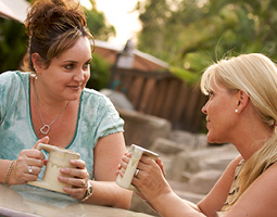 two women talking while drinking coffee