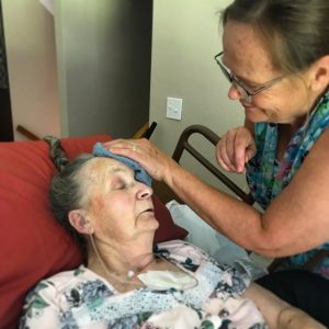 grandma's forehead gently caressed with a washcloth by her daughter