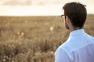 man staring at open field of grass